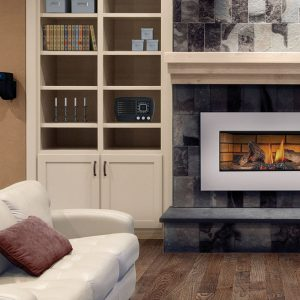 propane fireplace next to white couch and cabinet containing candles and a radio