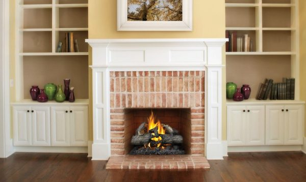 propane fireplace between white cabinets holding red and green vases