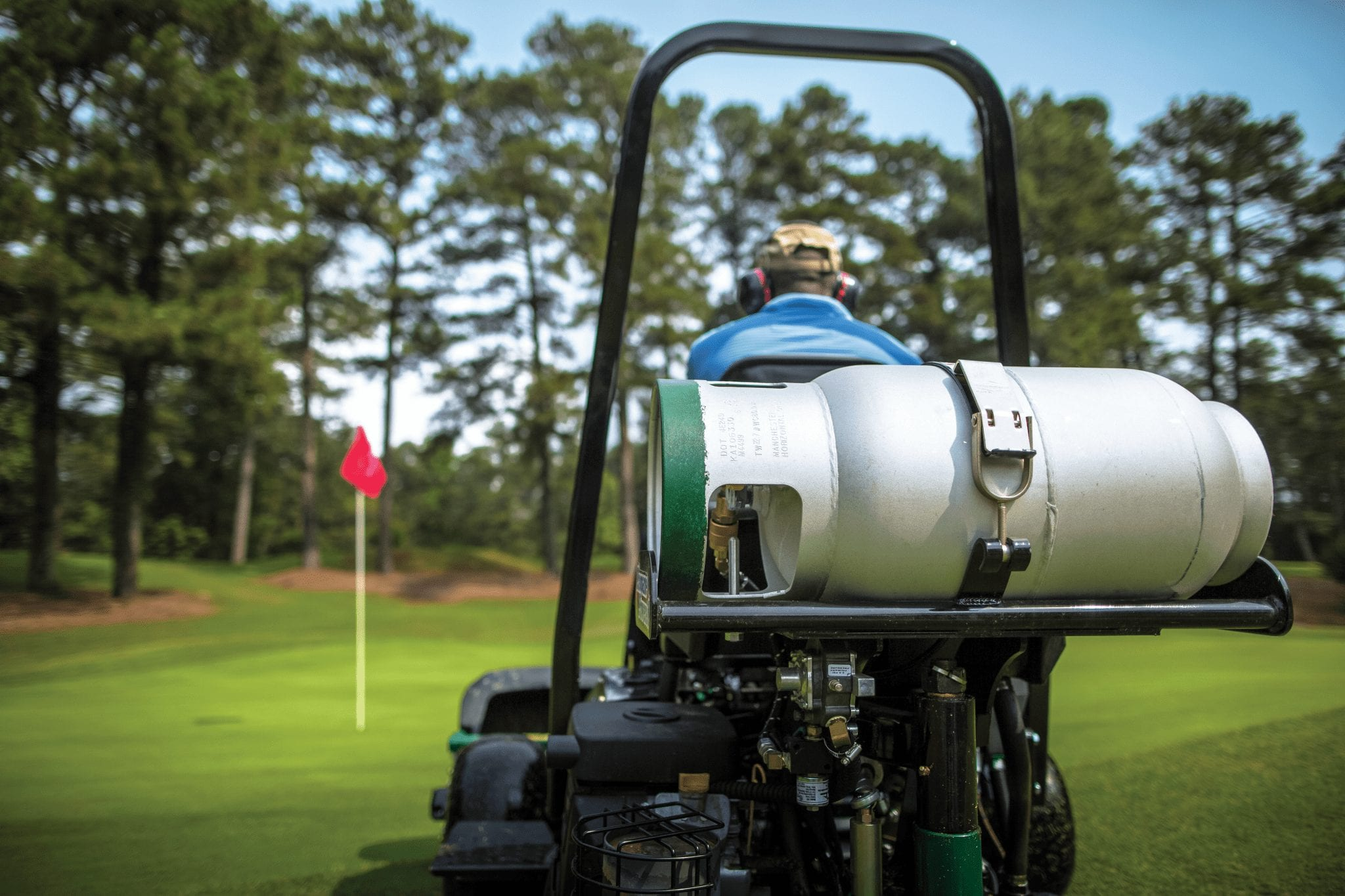 man mowing golf course with propane powered lawn mower