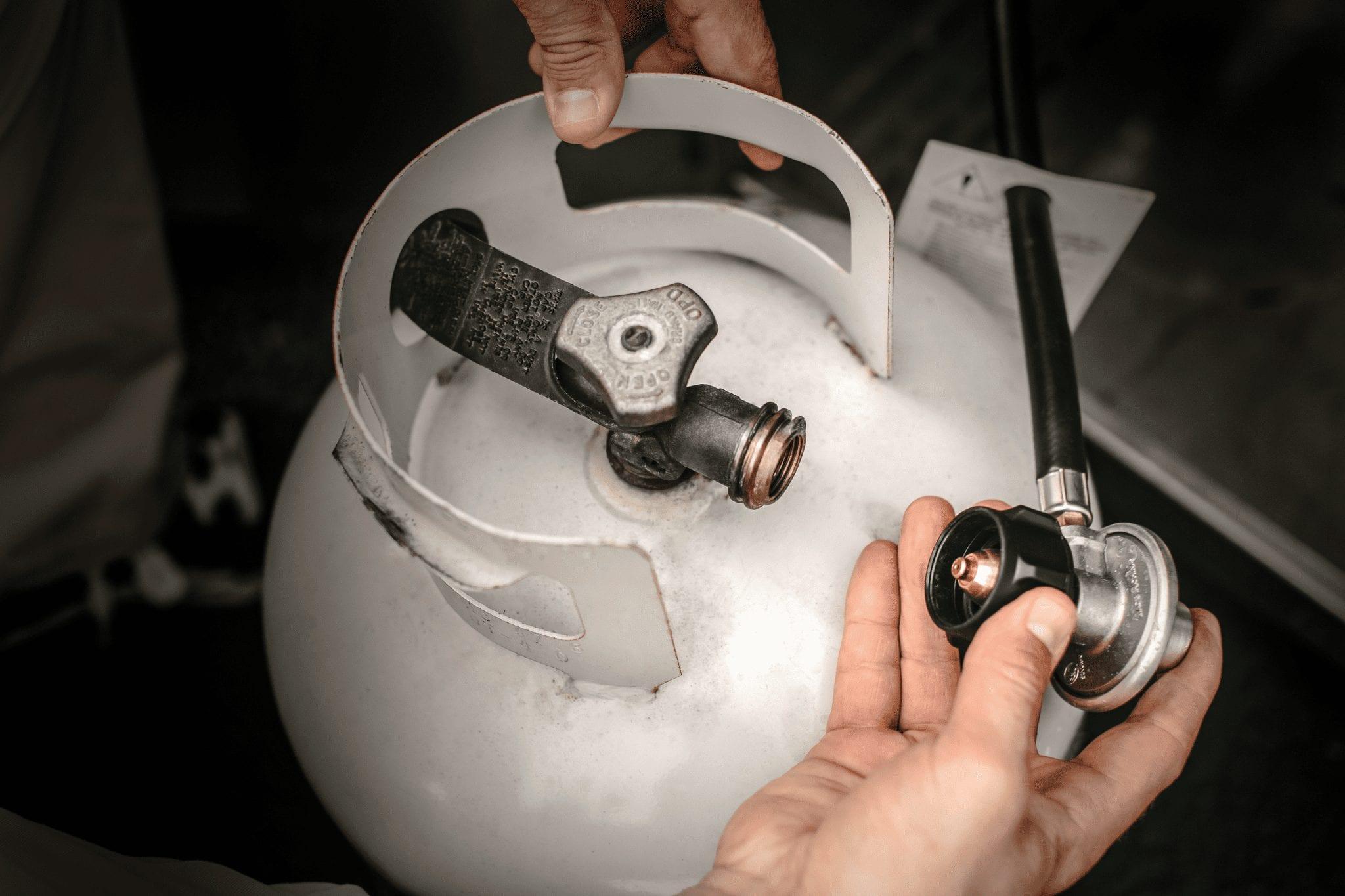 hands checking propane tank for leaks