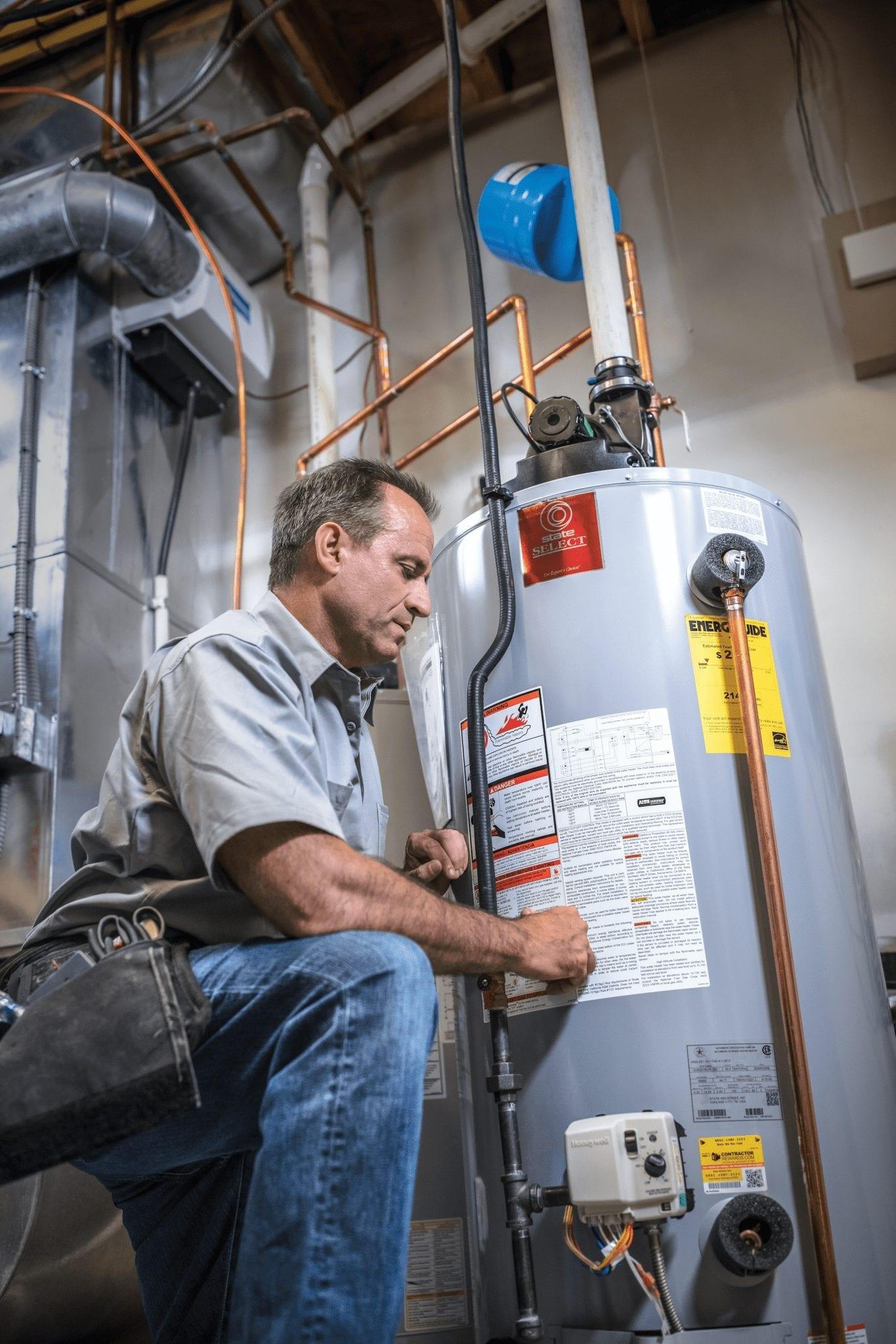 man in work uniform working on water heater