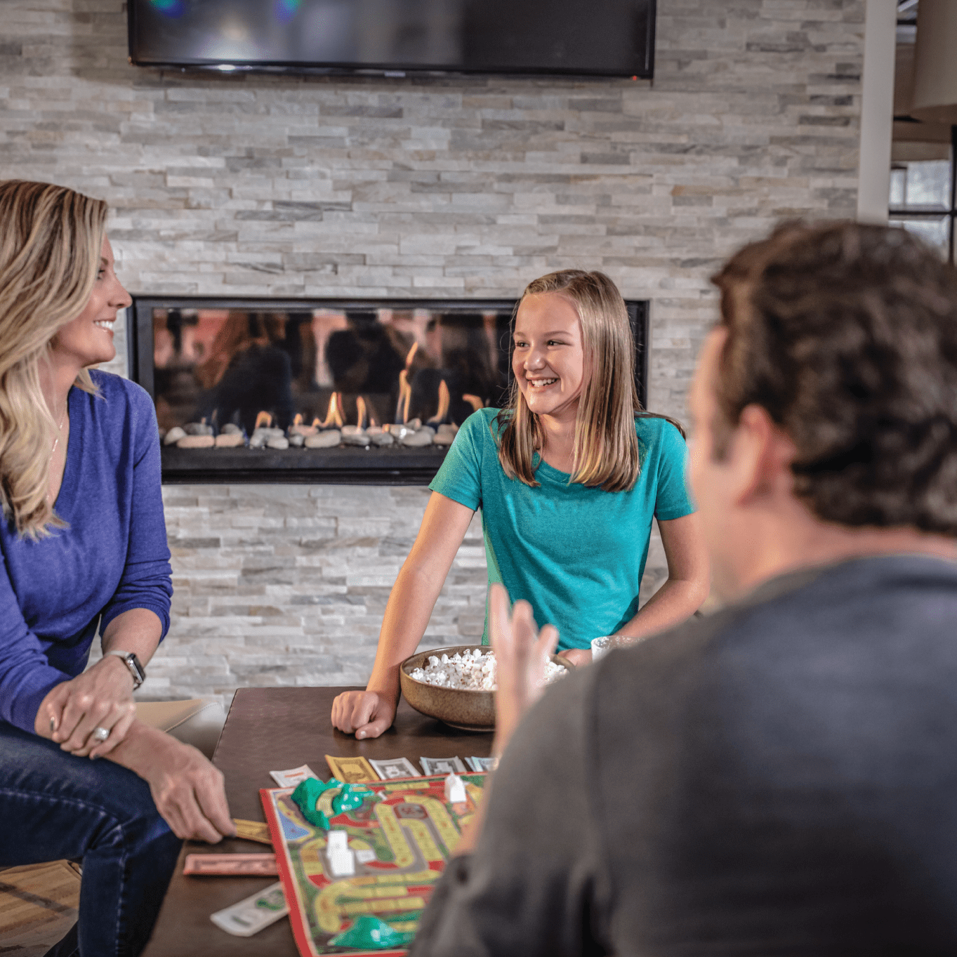 man, woman, and child playing board game near propane fireplace