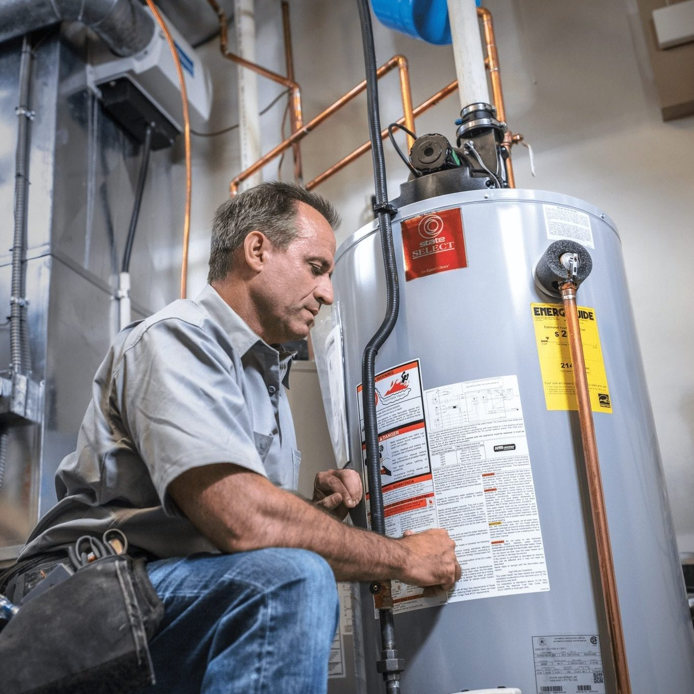 man in work uniform working on water heater